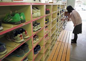 靴箱を見回るスクールソーシャルワーカー。気になる児童の靴の破れや汚れを見る=福岡市